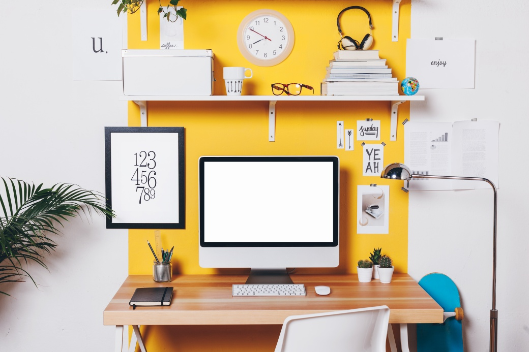 Modern creative workspace on yellow wall.